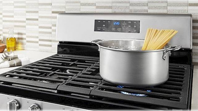 On a black cooktop, a bundle of pasta is getting cooked in a stockpot.