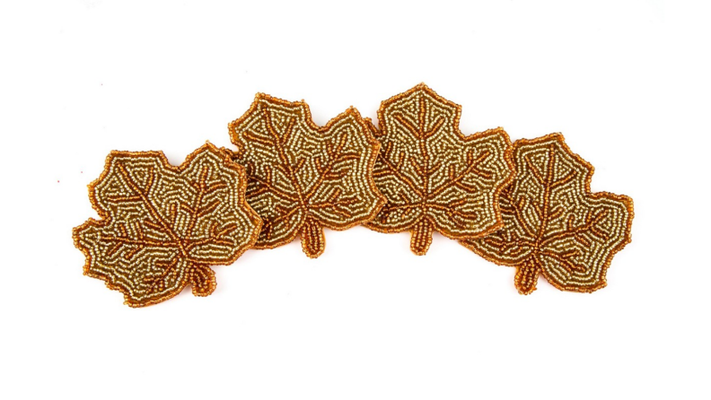 Four beaded coasters in the shape of autumn leaves.