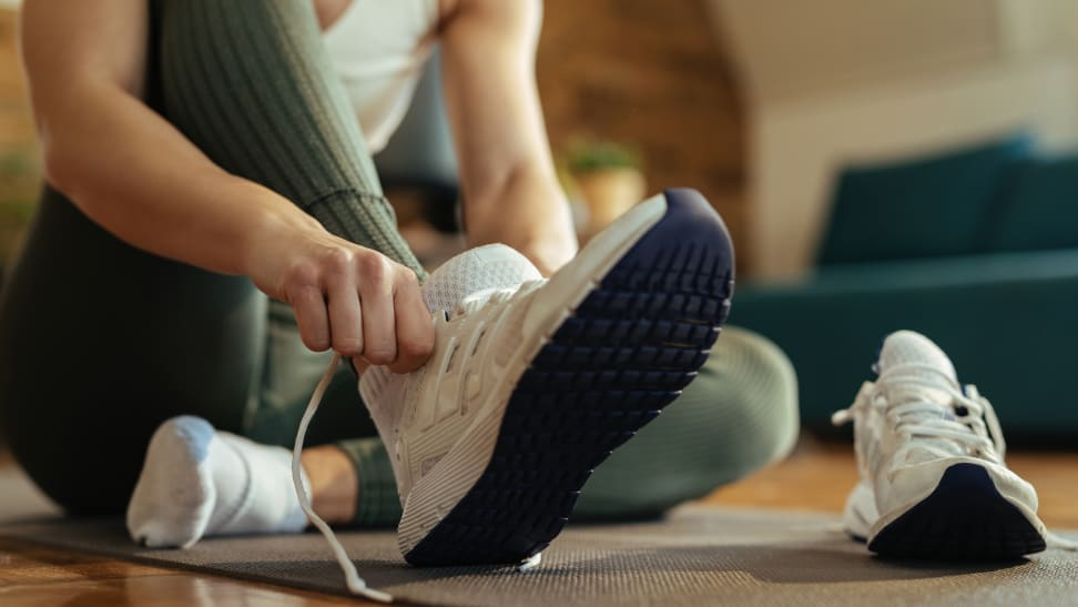 woman lacing up sneakers for exercise