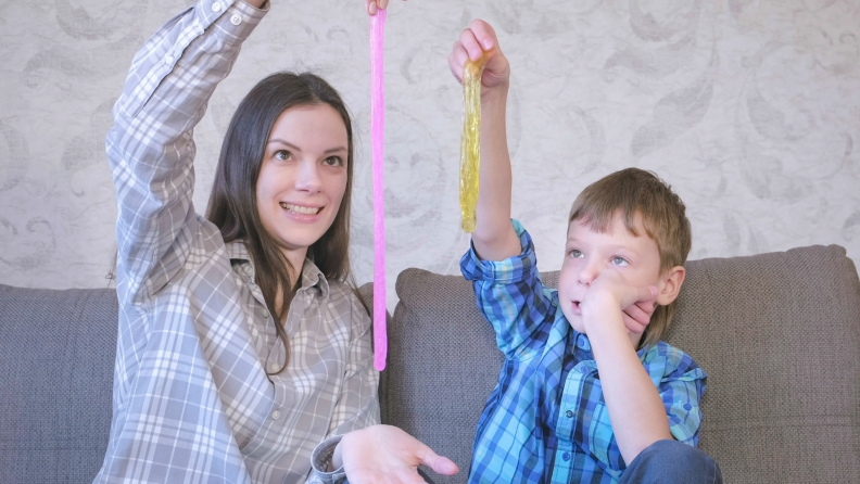 Smiling mom and son are playing with slime sitting on the sofa