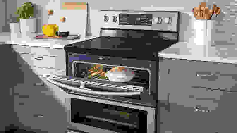 The  Samsung NE59J7850WS electric range shown with it's top oven door open. There is a lemon meringue pie in the oven.