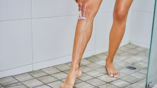 A person shaves their legs with a razor inside a shower stall.