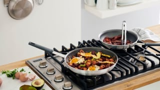 A brightly lit kitchen featuring a gas cooktop with two frying pans filled with food.