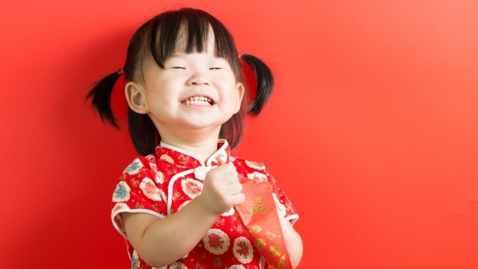 Little Asian girl joyfully holding red envelope on red background