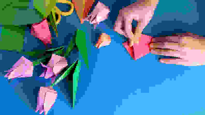 Bouquet of tulips from origami colored paper on a blue background.