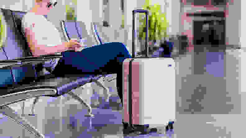 A woman sitting at an airport with a pink hard sided rolling suitcase next to her