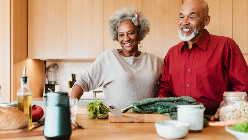 A couple speaks to a smart speaker as they make a meal in their kitchen.