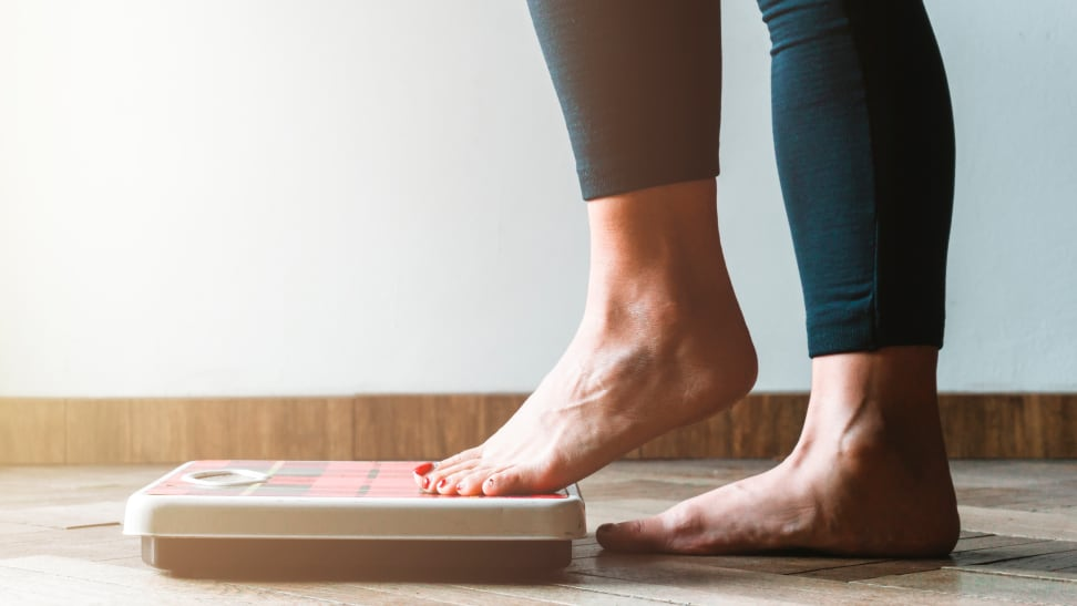 person in black leggings stepping on a scale