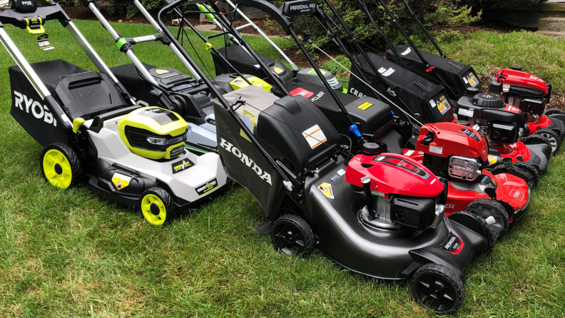 Eight lawn mowers sit on a green lawn.