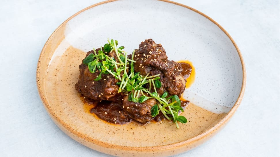 A white and orange plate filled with braised oxtail and topped with micro greens.