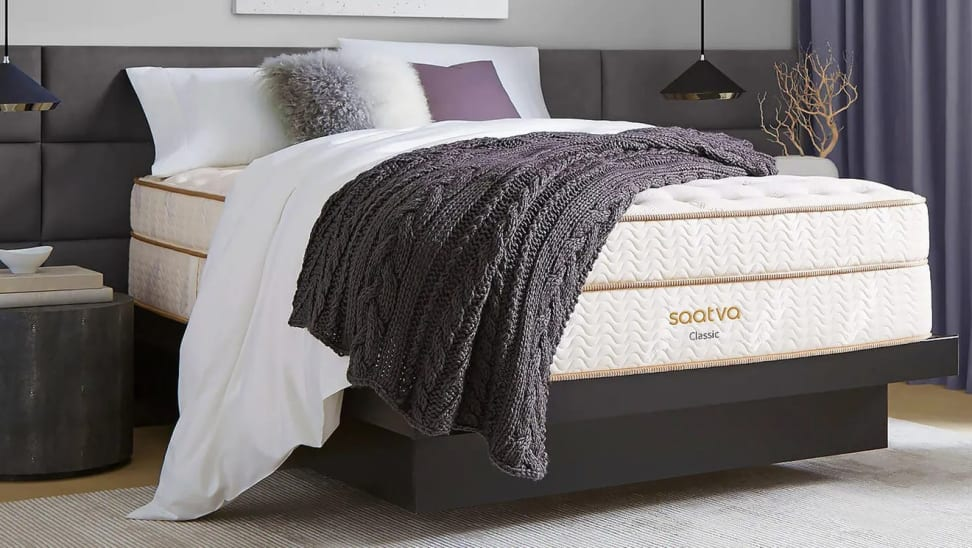 Image of a bedroom with a Saatva mattress covered with pillows and a throw blanket.