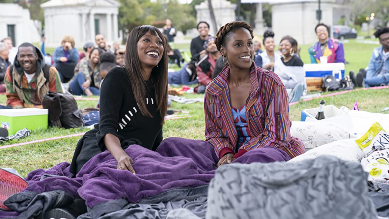 A still from the series Insecure featuring Issa Rae and Yvonne Orji sitting on a picnic blanket.