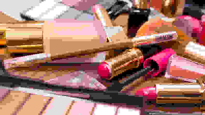 Used makeup, including an eyeshadow palette, eyeliner, foundation, and lipsticks, lay haphazardly across a table.