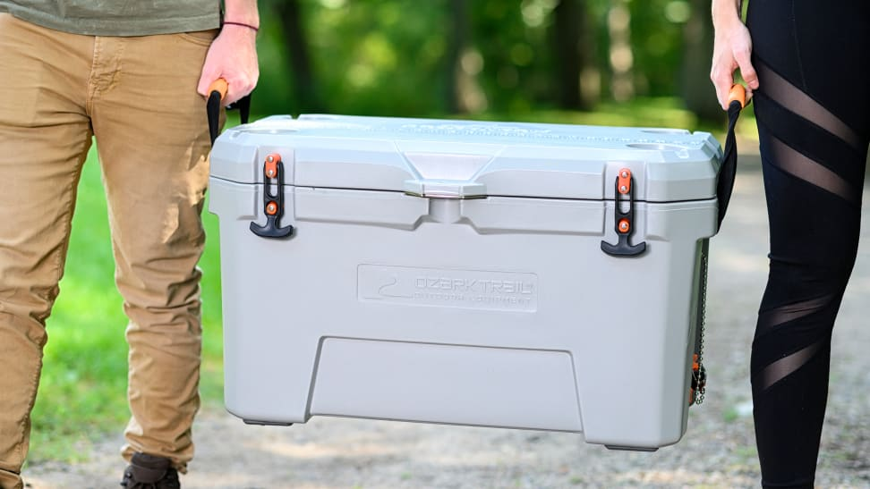 A man and a woman carrying an Ozark Trail cooler.