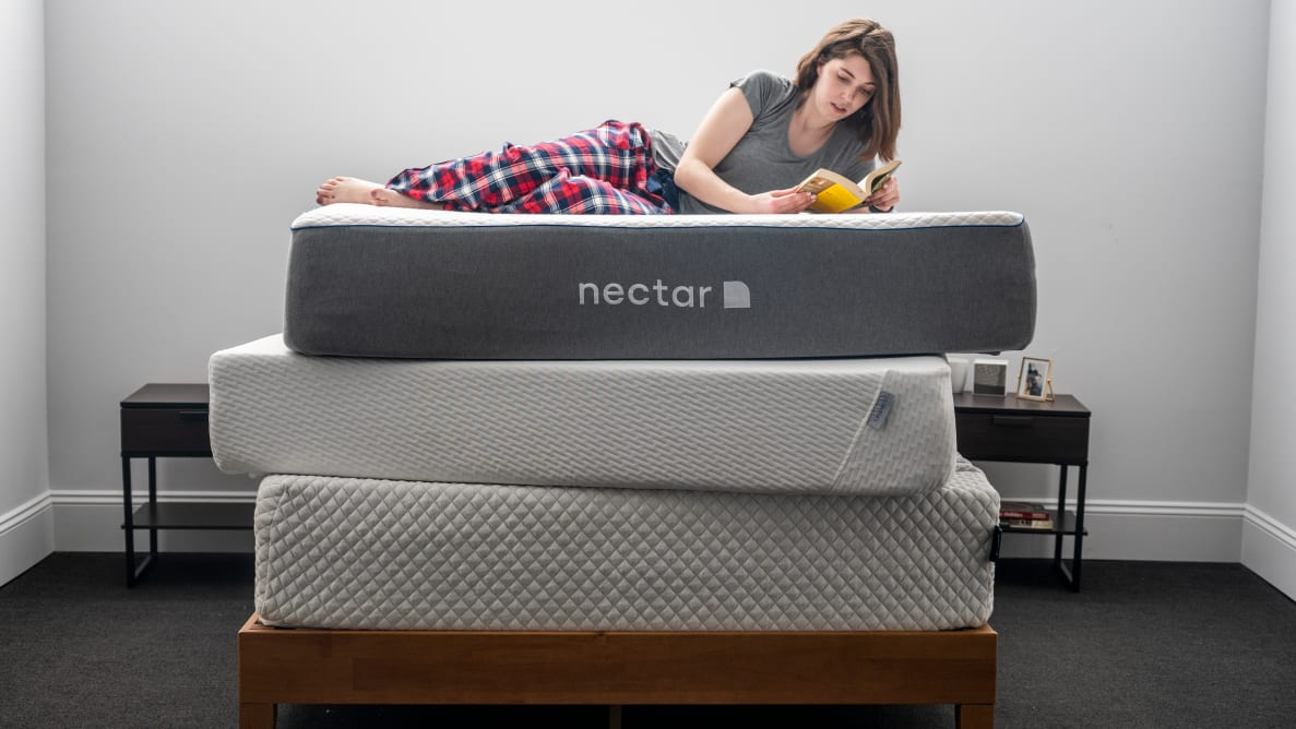 a woman lies down on a stack of mattresses reading