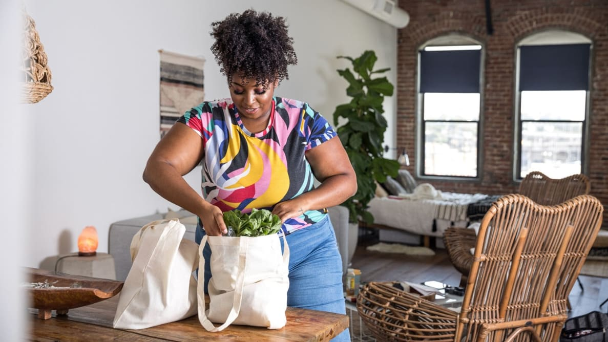 A woman storing groceries she paid for with a credit card
