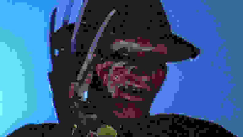 A close-up of Freddy Krueger, with bladed glove partially covering his face, from