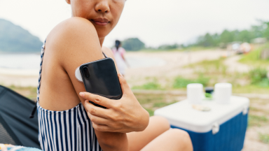 Person using smartphone to check diabetes monitor on arm.
