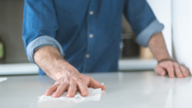 A man cleans a countertop with a disinfecting wipe
