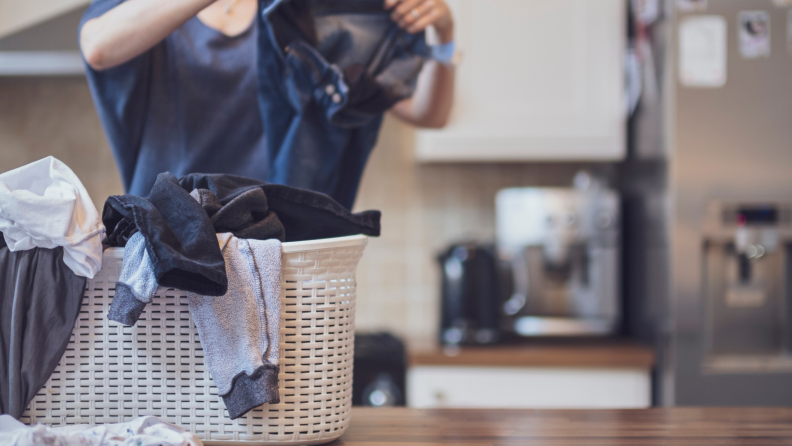 A person sorts laundry on a kitchen countertop.