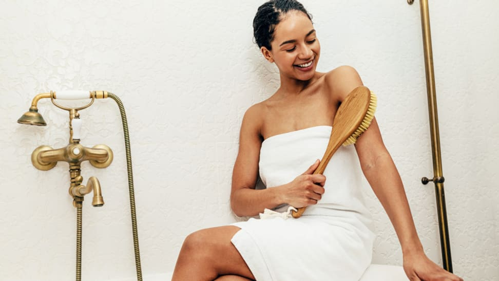 A woman sitting on the edge of a tub dry brushing her arm