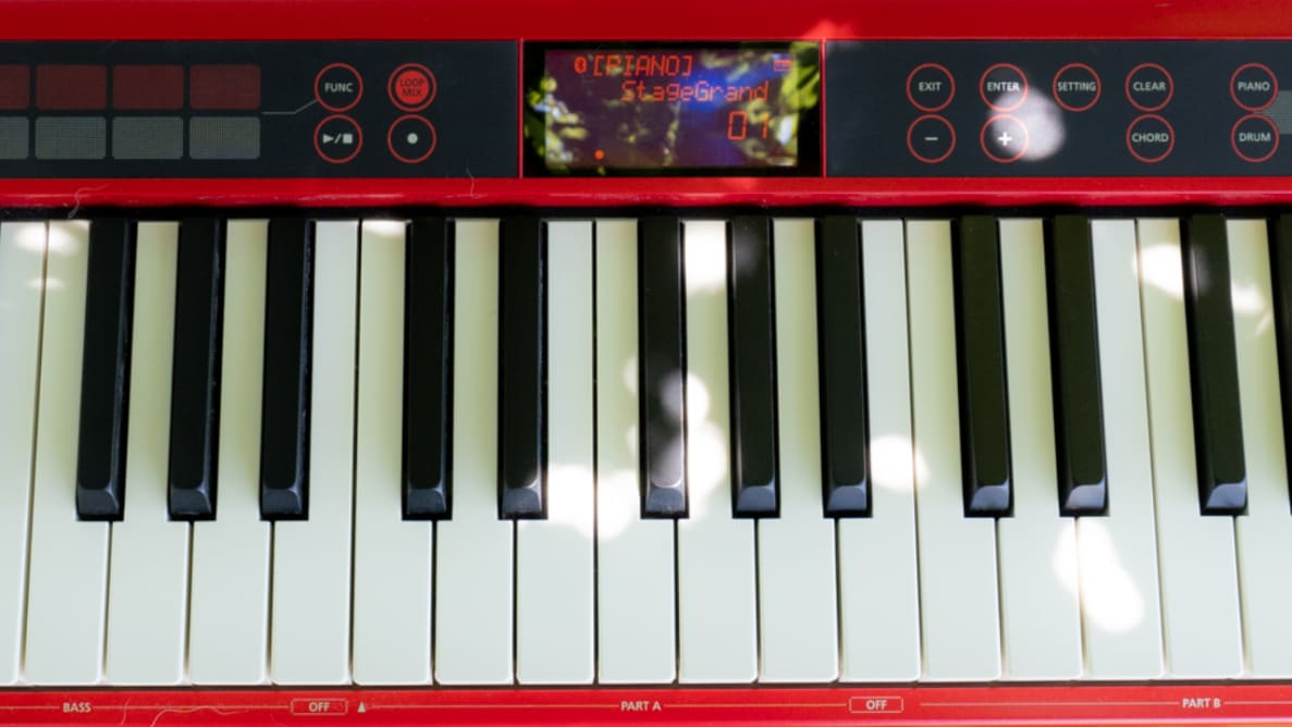 A closeup of a red Roland piano keyboard, with black and white keys