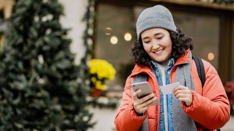 Woman in winter jacket shopping for holiday gifts