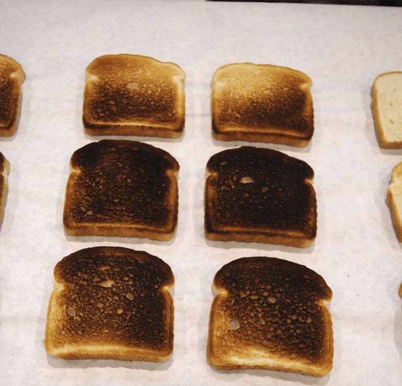 Six slices of toast that have been in the broiler.