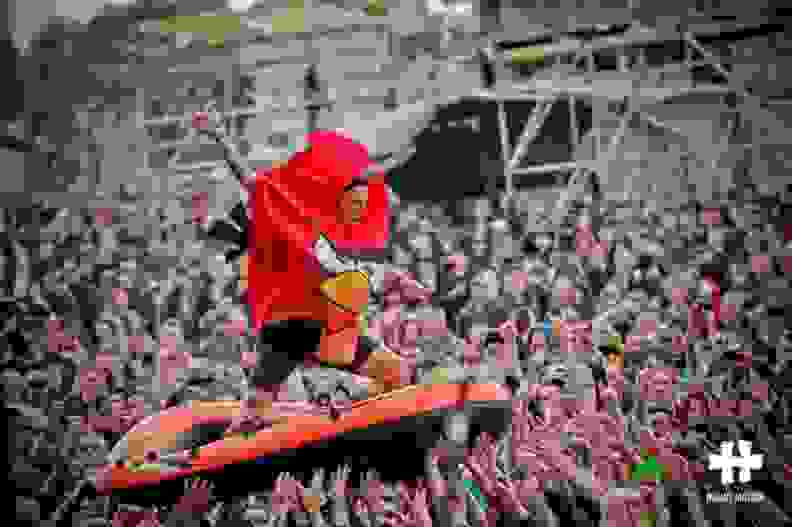 Adam crowd surfing in a raft while wearing an Angry Bird costume.