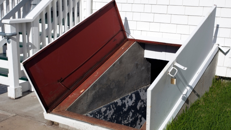 A storm cellar with open doors leading to underground shelter