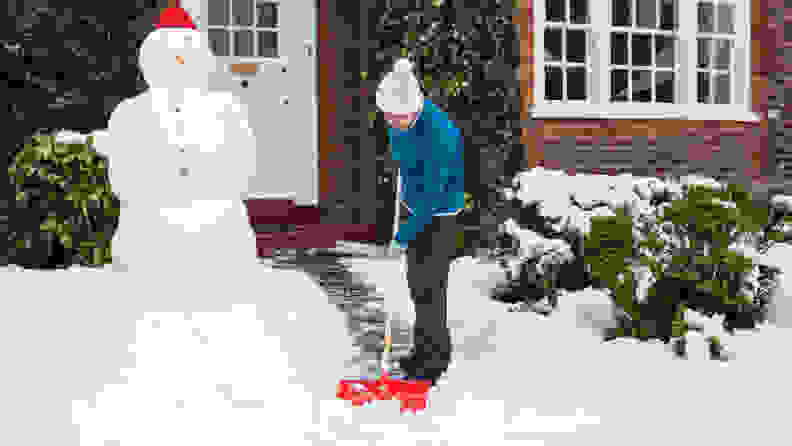 Woman shovels snow outside her home in UK