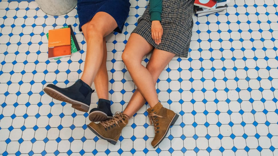 Two girls with boots on sitting on a tile floor.