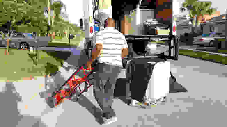 A man wheels a dolly over to an appliance that's sitting outside the open back of a delivery truck.