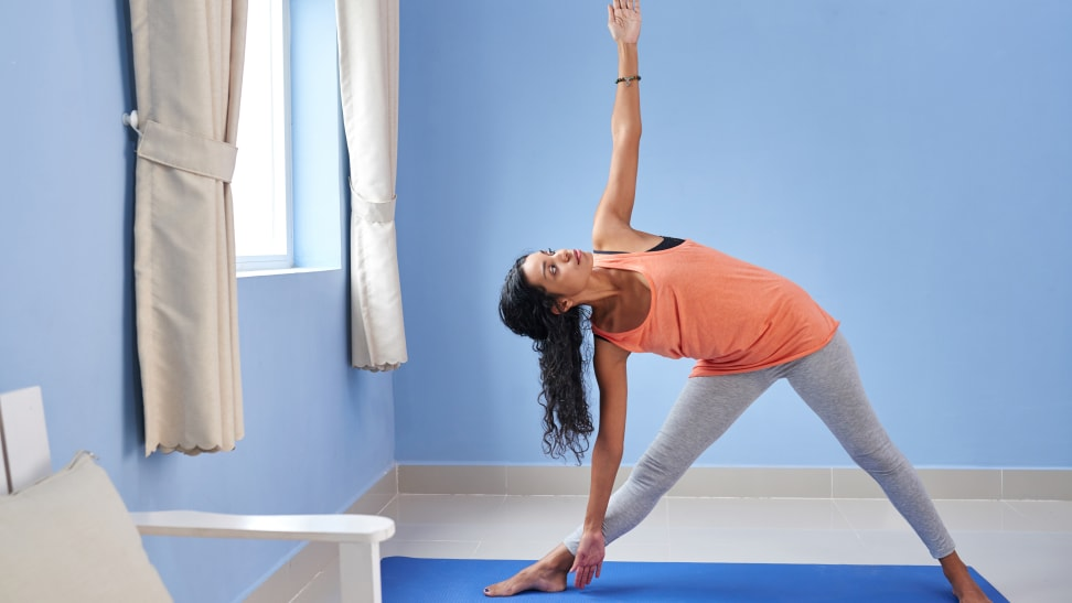 Woman practicing yoga in blue room.