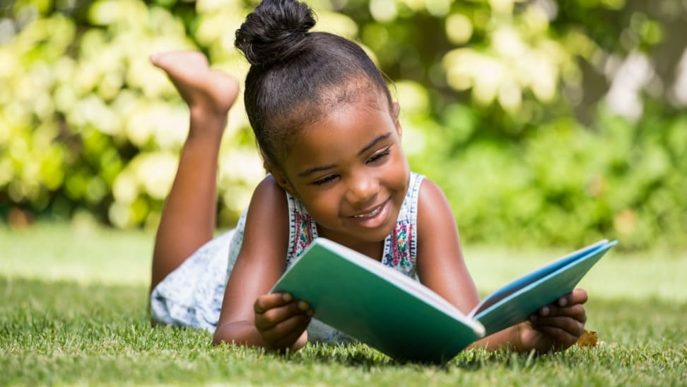Young girl reading book outdoors in the grass while smiling
