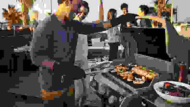 Man grilling meat on an open grill next to his friends.