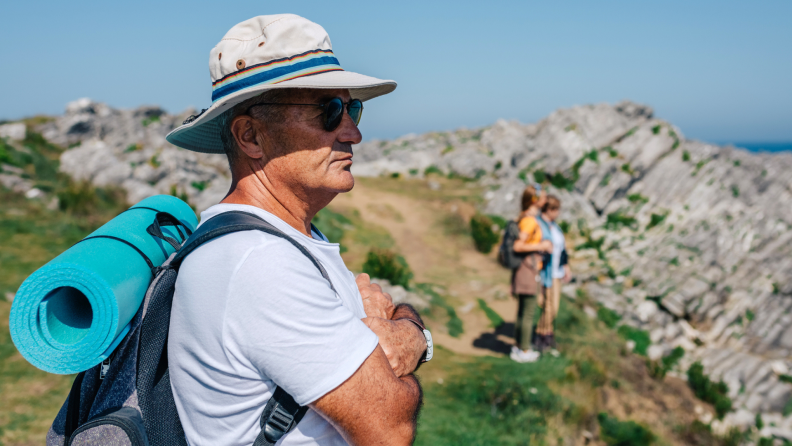 A person wearing a hat looks over a cliff.