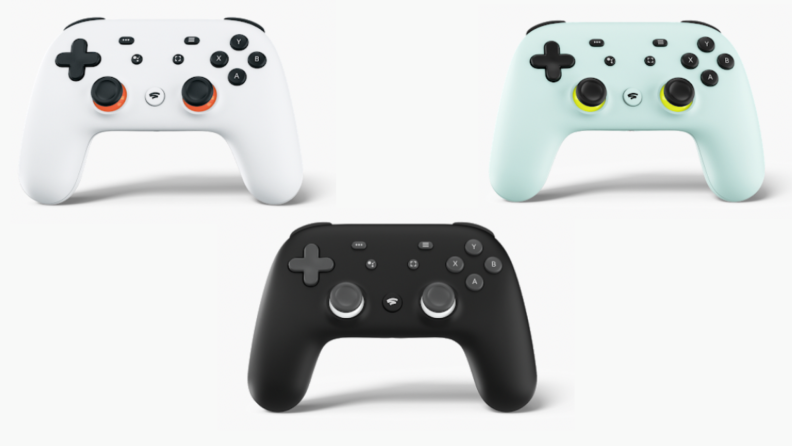 Three Google Stadia controllers in white, black and green shades.