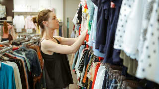 Woman looking through racks of used clothing at a thrift store.