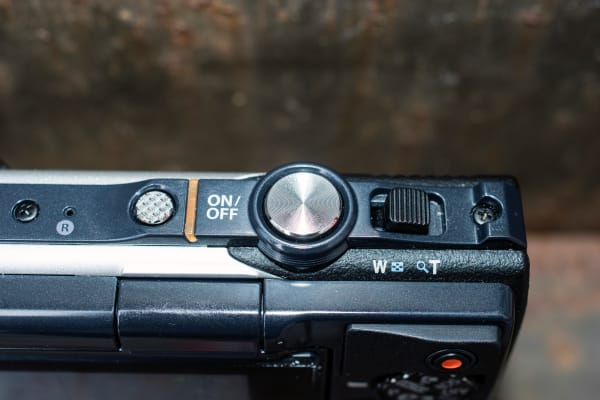 Top controls are power switch, shutter release, and the zoom toggle.