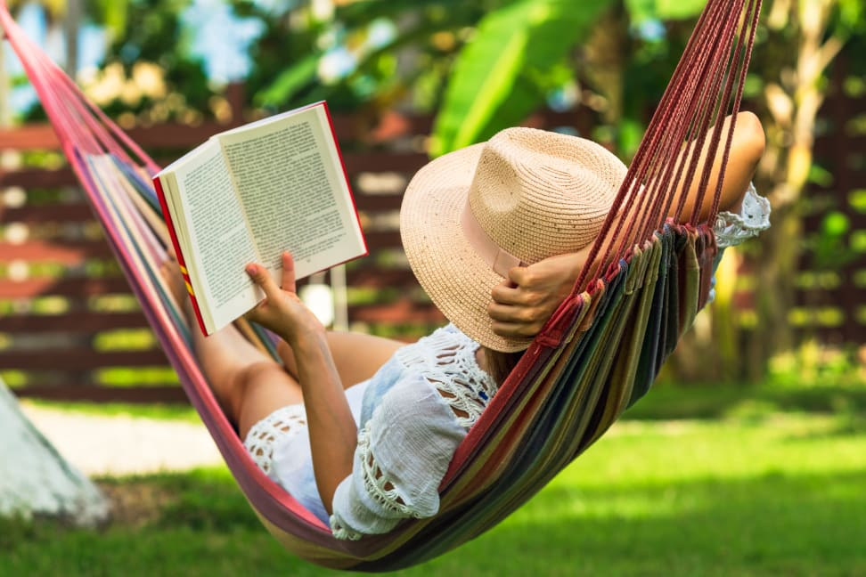 Woman wearing white dress and tan straw hat laying in multi-colored hammock outside while reading a book.