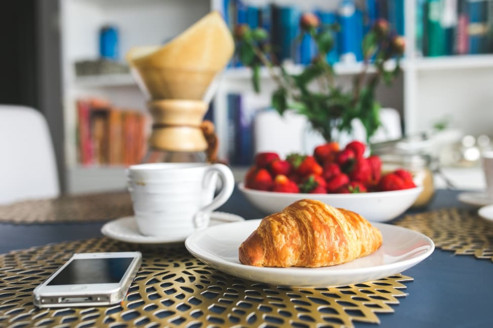 Coffee, strawberries, a croissant, and a smarpthone
