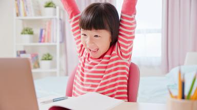 Little girl having fun on a laptop computer.