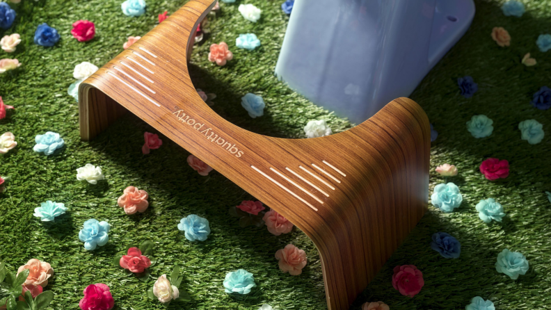 Wooden Squatty Potty sitting in front of toilet on grass surrounded by flowers.