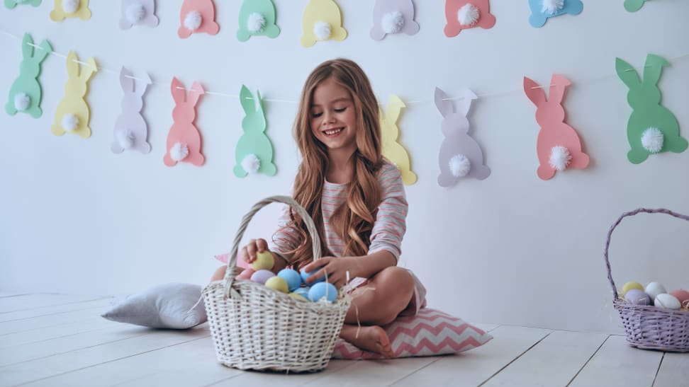 A girl sitting on the floor putting eggs in her Easter basket