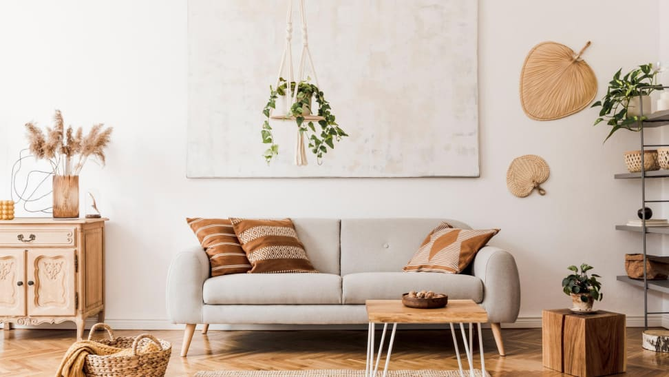 Neutral modern and cozy living room with warm brown accents and a hanging plant over the a gray couch