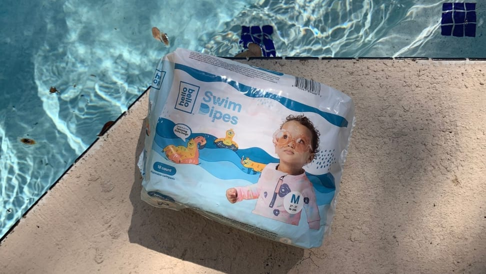 A pack of Hello Bello Swim Dipes sits on a pool deck.