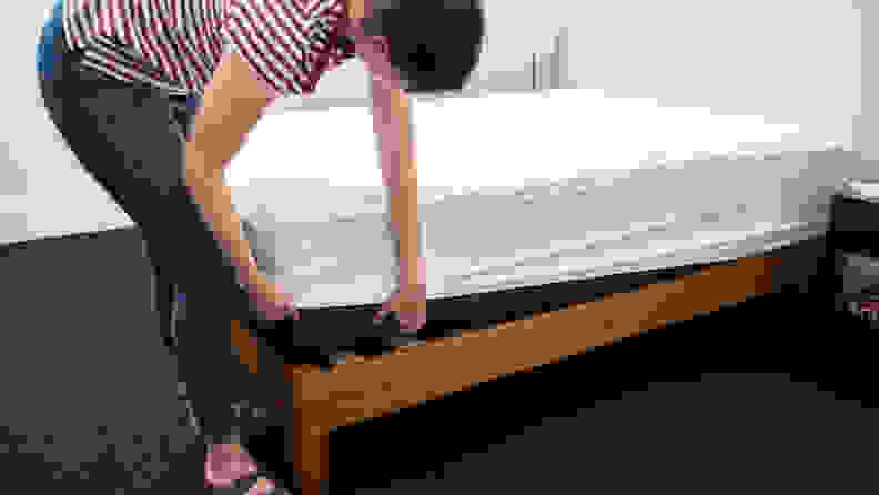 A person pulls a mattress protector over the edge of a bare mattress