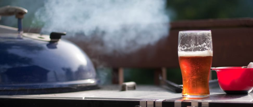 A pint glass of beer sits next to a smokey grill