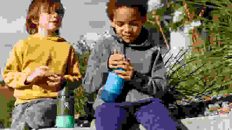 Two boys sit on a bench holding water bottles